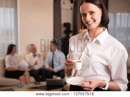 Enjoyable time. Cheerful positive delighted woman holding cup and drinking coffee while her colleagues sitting on the couch in the background