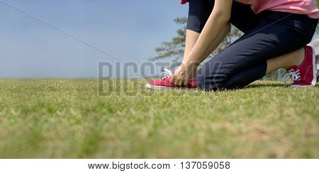 young Asian woman tying shoelace, park, nature