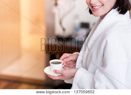 Unforgettable taste. Cheerful delighted smiling woman sitting on the bed and drinking coffee while expressing gladness