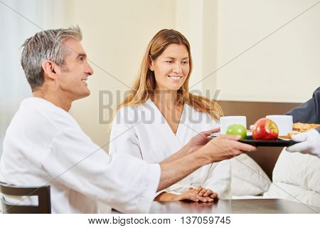 Room service bringing breakfast in bed for happy elderly couple in a hotel room