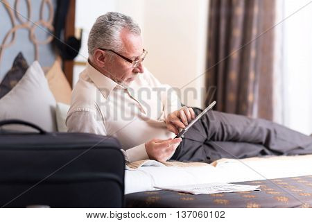Get some rest. Delighted senior man lying on the bed and using tablet while resting