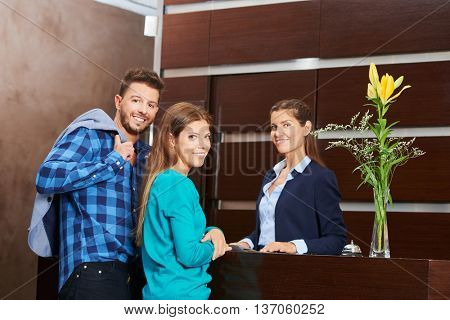 Young couple with receptionist during hotel check-in at the reception