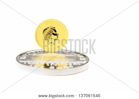 Golden dollars coin standing on silver bullion isolated on white background