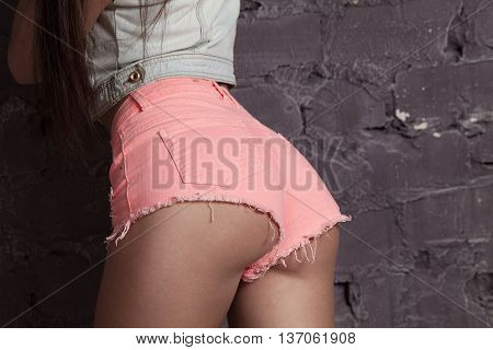 Perfect buttocks and body. Close-up of perfect female buttocks in jeans shorts
