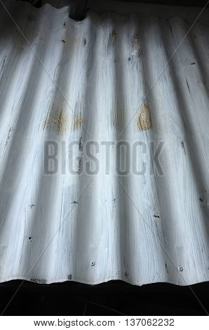 Texture of silver corrugated metal with bolts