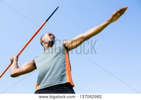 Low angle view of determined athlete about to throw a javelin in the stadium