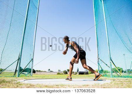 Athlete throwing discus in stadium during competition