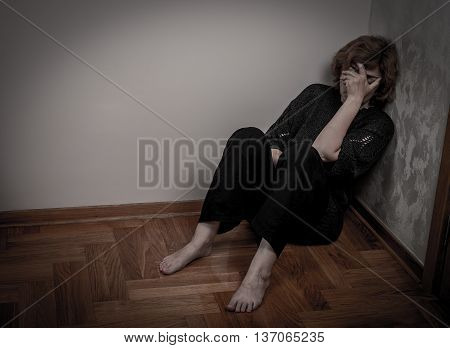 Depressed and sad woman sitting on the floor in the empty room. Low key.