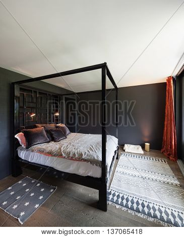 Wooden canopy bed and hardwood floor, black walls