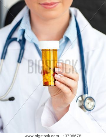 Close-up of a female doctor holding pills into the camera in her office