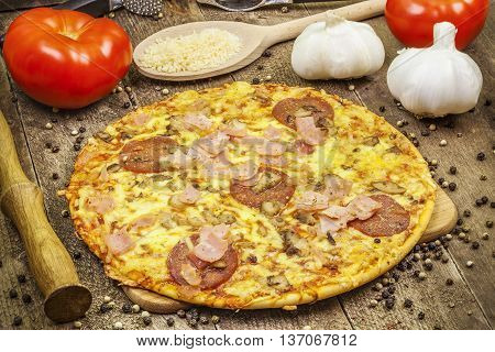 Pizza wit bacon and salami near tomatoes and garlic on wooden table