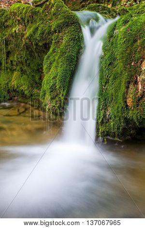 small waterfall among green stones