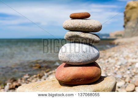 balanced stone pyramid of pebble on sea