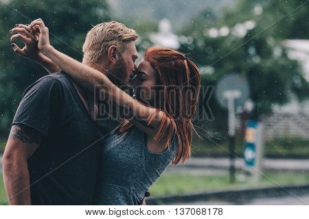 beautiful couple kissing outside in the rain