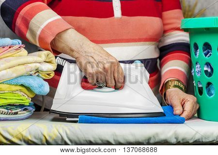 Ederly woman ironing in room summer day