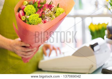 people, shopping, sale, floristry and consumerism concept - close up of florist man holding bunch wrapped in paper and counting price at flower shop cashbox