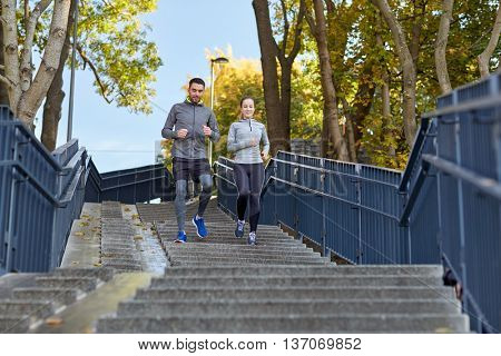 fitness, sport, people and lifestyle concept - happy couple running downstairs in city