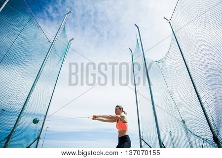 Female athlete performing a hammer throw in stadium