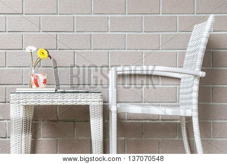 Closeup artificial colorful flower on glass bottle and computer on wood weave table with wood weave chair on blurred brown brick wall texture background beautiful interior in relaxation concept