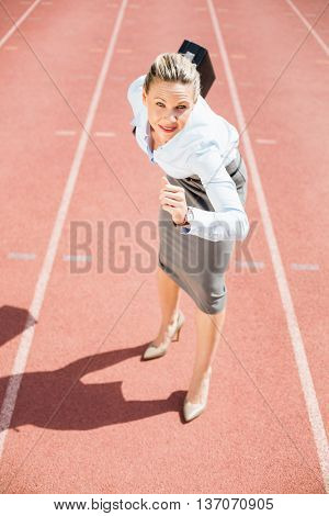 Portrait of businesswoman with briefcase in ready to run position on running track
