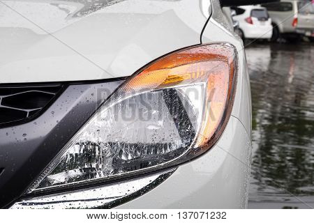 Close up headlight of white car with Water drops on. Car lamp.