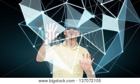 3d technology, virtual reality, entertainment and people concept - happy young in with virtual reality headset or 3d glasses with low poly shape projection over black background