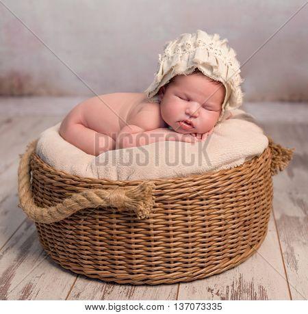 cute newborn baby with hat sleeping in wicker basket
