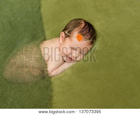 bare newborn baby with headband lying on a green blanket
