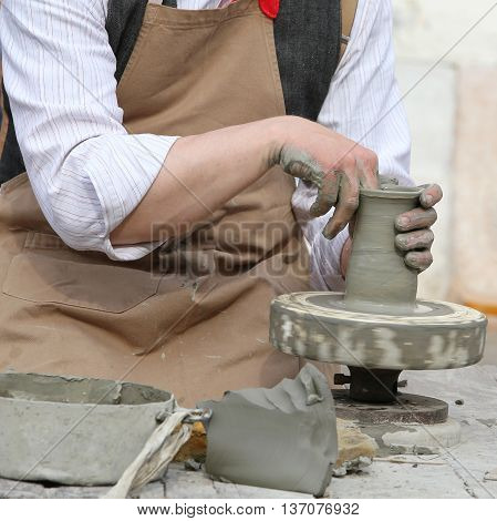 Potter With The Hand Lathe During Production Of A Pot With Clay