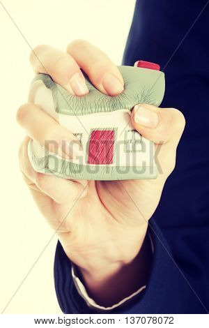 House model being squeezed in woman's hand.