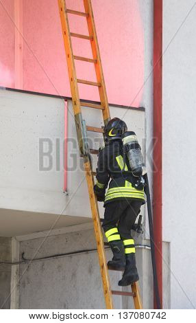 Firefighter With Oxygen Cylinder Wood Climbing A Ladder