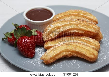 Churros on blue plate with chocolate sauce and strawberry