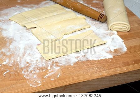 Dough preparing for baking on brown wooden cutting board on kitchen table. Closeup view