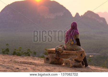 Lonely woman sitting on wooden bench at view point.