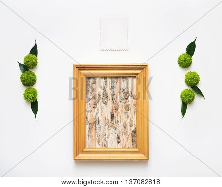 Wooden frame with collage of birch bark and paper with decoration of chrysanthemum flowers and ficus leaves on white background. Overhead view. Flat lay.