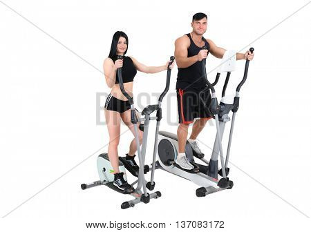 young pair of woman and man doing exercises with elliptical trainers together, isolated on white background