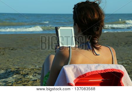 woman with brown hair reads the ebook on the beach