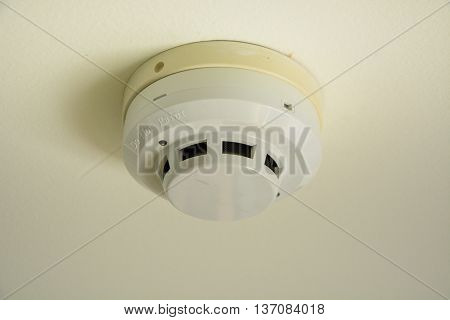 a fire smoke sensor on room ceiling
