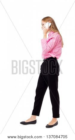 side view of a woman walking with a mobile phone. back view ofgirl in motion.  backside view of person.  Isolated over white background. Woman office worker in a pink shirt is right on the phone.