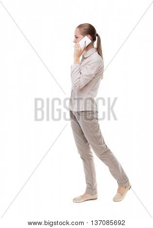 side view of a woman walking with a mobile phone. back view ofgirl in motion.  backside view of person. Isolated over white background.  girl in a white jacket is talking on a white smartphone