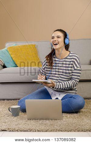 Beautiful woman at home studying while listen music