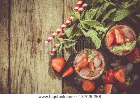 Strawberry mojito and ingredients on rustic background, copy space, toned
