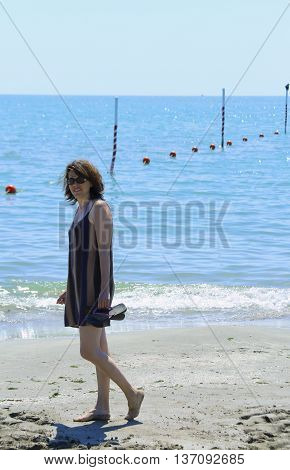 cute smiling woman walking on the beach by the sea in summer