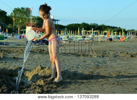 Pretty Little Girl Play With Bucket And Water In The Beach