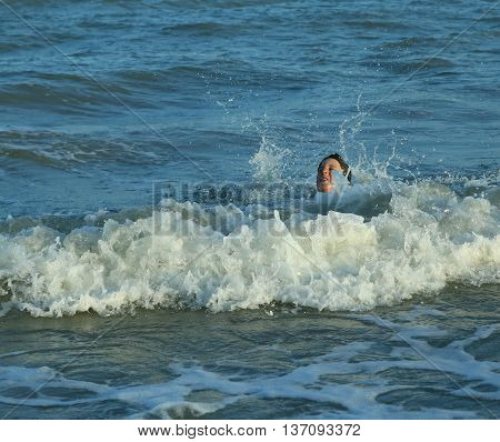 Young Boy Plays By Jumping The Waves Of The Sea In Summer