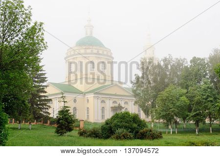 Russian Orthodox church and green trees in morning haze Orel Russia horizontal