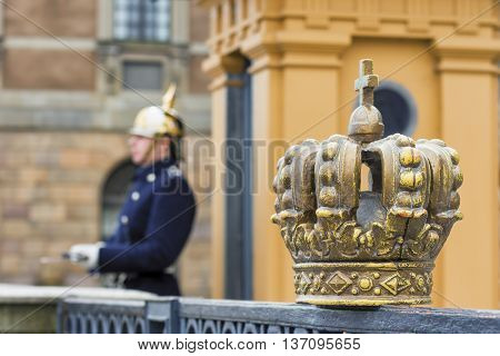 STOCKHOLM, SWEDEN - MARCH 30, 2016: Swedish royal crown and soldier Royal Guard blurred in the background at the Royal Palace Square in Stockholm