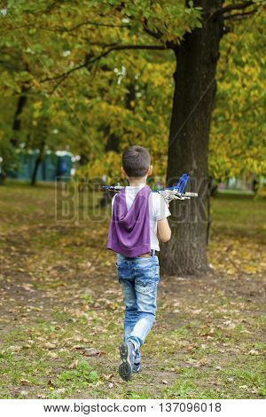 Portrait of a pretty brunette little Boy holds model airplane in autumn park