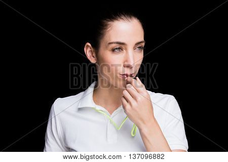 Female athlete blowing a whistle on black background