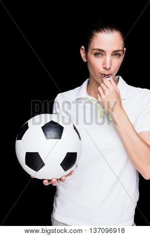Female athlete blowing a whistle and holding a soccer ball on black background